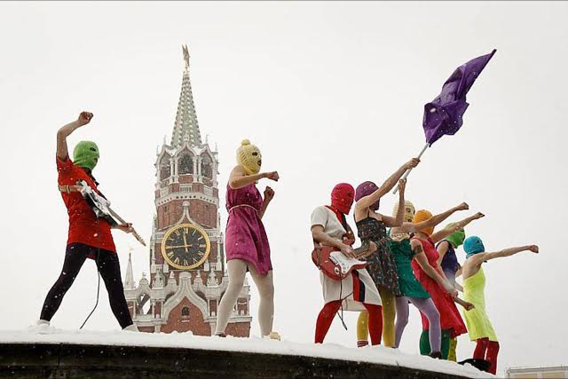 Pussy Riot waving flags in front of steeple