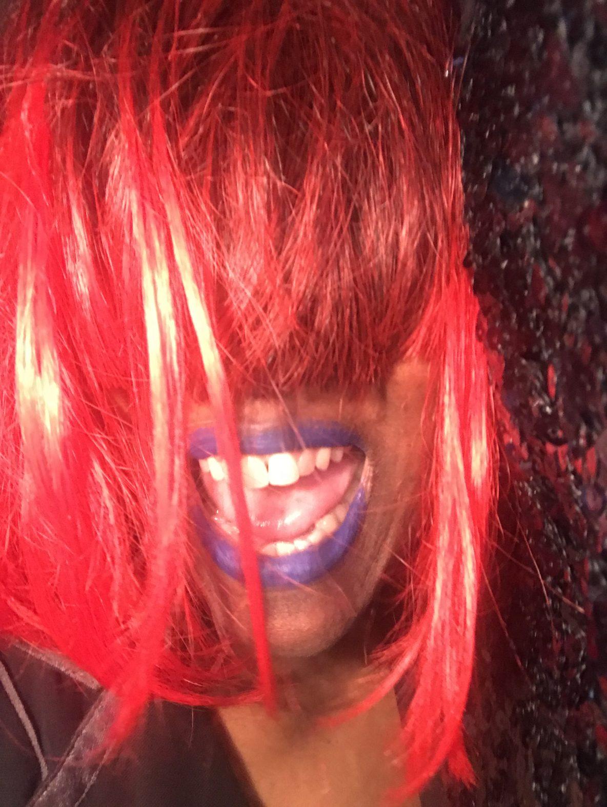"Marya Errin Jones in, ""Ask An American,"" wearing a red wig and purple lipstick"