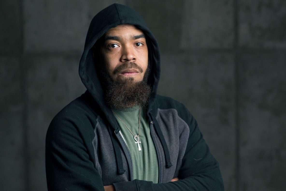 Frank Green, director of Hype Man: A Break Beat Play, in a green shirt and black hoodie, posed with arms crossed against a concrete wall