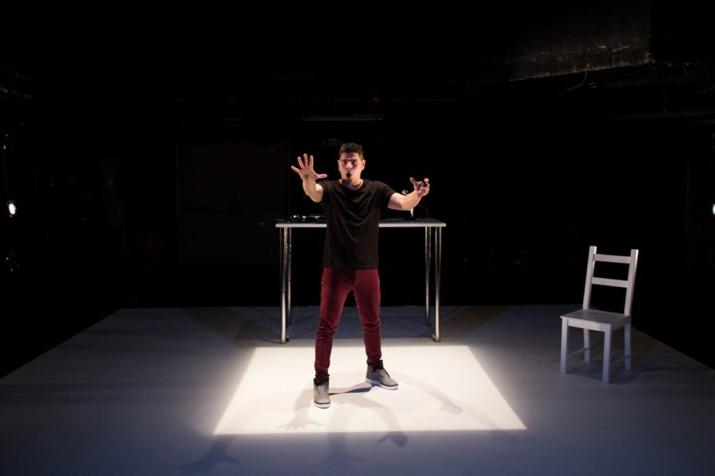 """Brian Quijada in a square of white light in his one-man show, """"Where Did We Sit On The Bus?"""""""