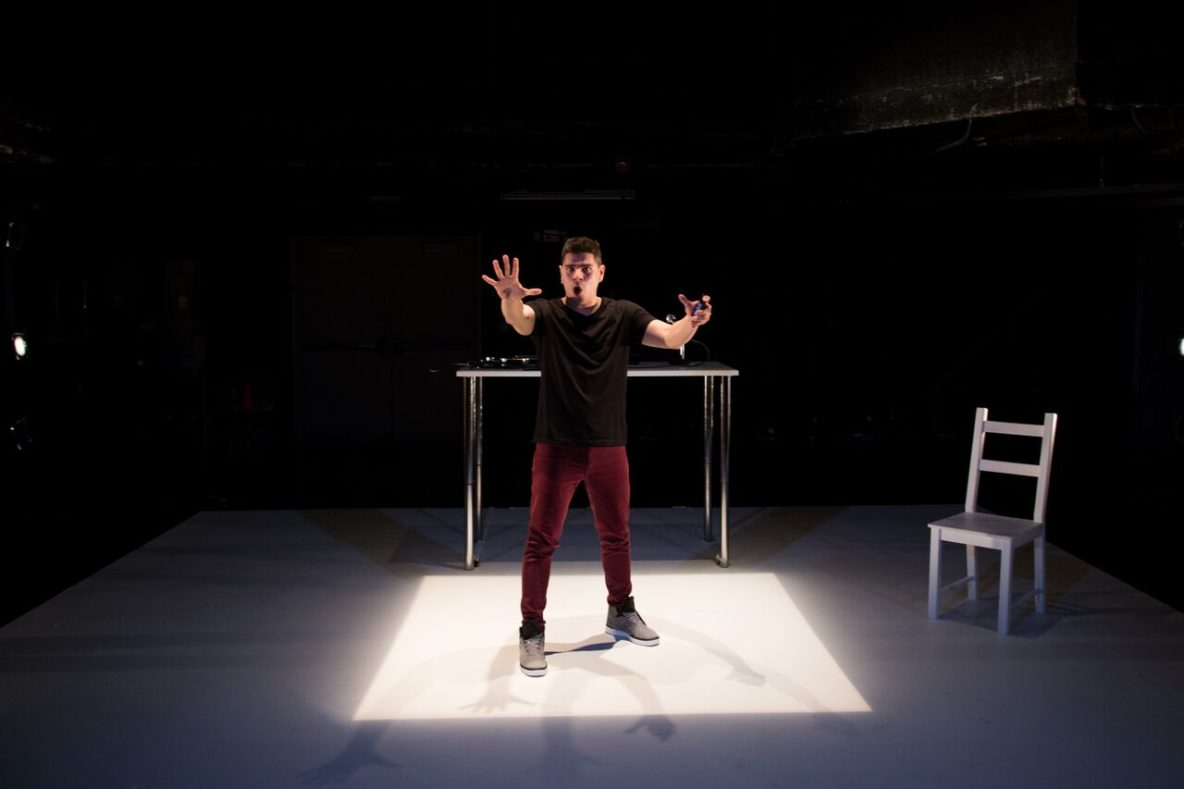 "Brian Quijada in a square of white light in his one-man show, ""Where Did We Sit On The Bus?"""